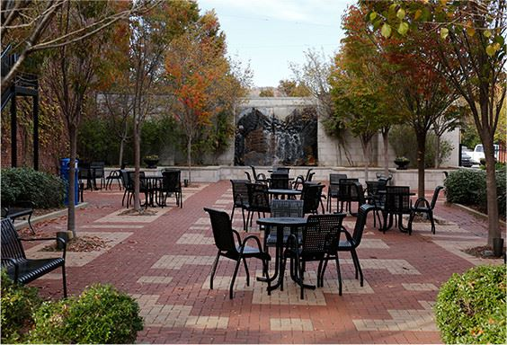 Several cast-iron chairs  and tables on a brick patio with trees