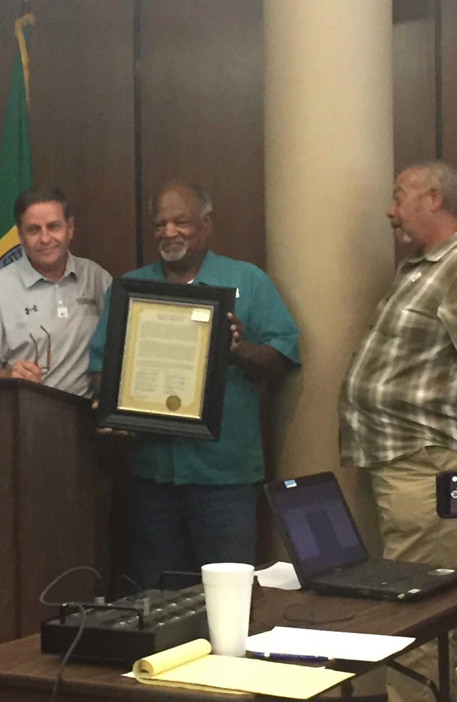 Curlie DeRamus receives his Quality of Life proclamation from Mayor Sherman Guyton.